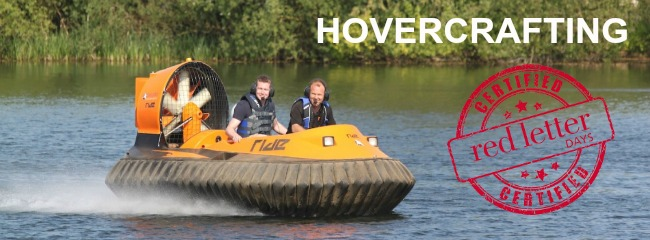 Two men driving a hovercraft over a lake and smiling.