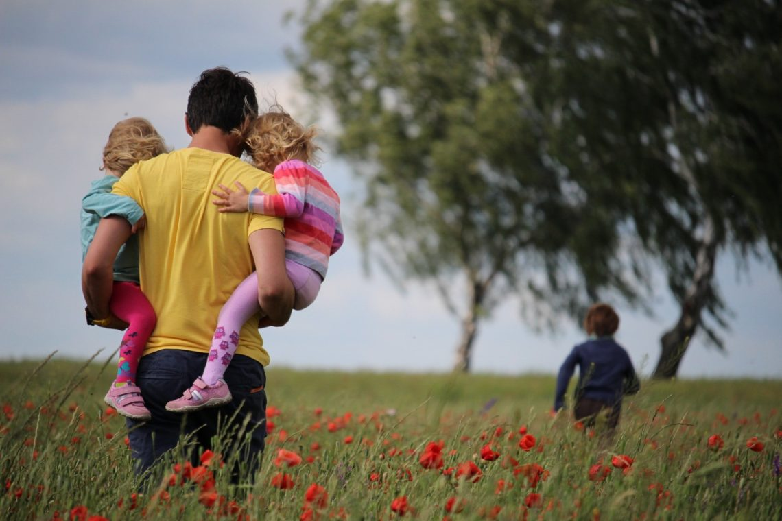 father and his kids in a field