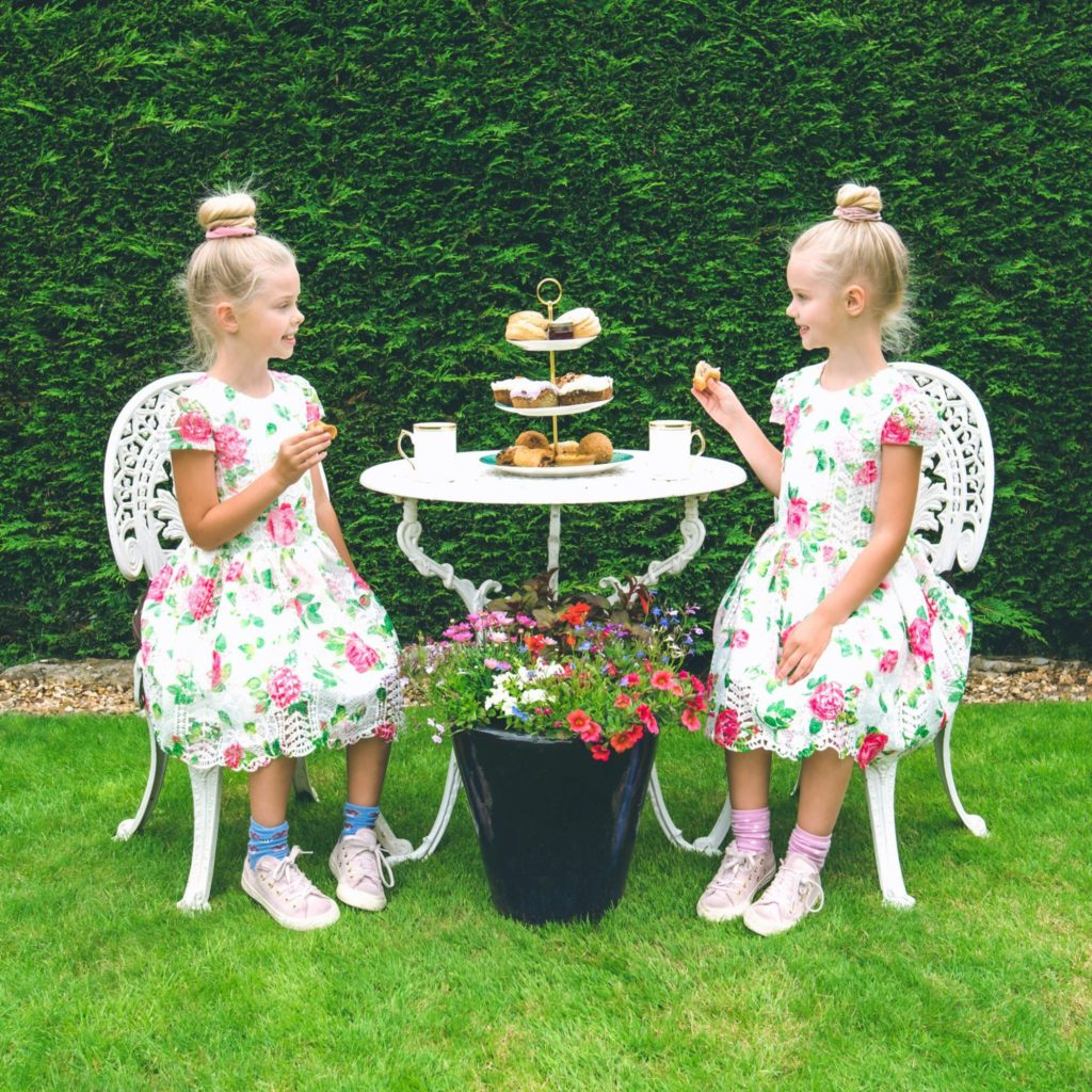 two young girls enjoying afternoon tea in the garden