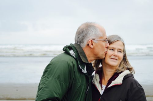 older man kissing his wife on the cheek