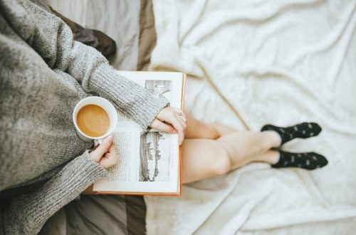 woman reading a book an enjoying a hot drink