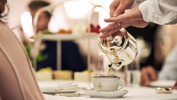silver tea pot pouring tea into a Harrods tea cup