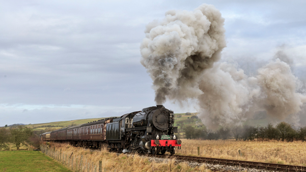 steam train giving off lots of steam in surrounding countryside