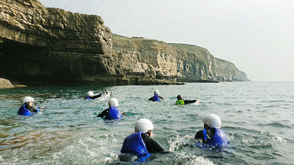 a group of people coasteering next to a large cliff